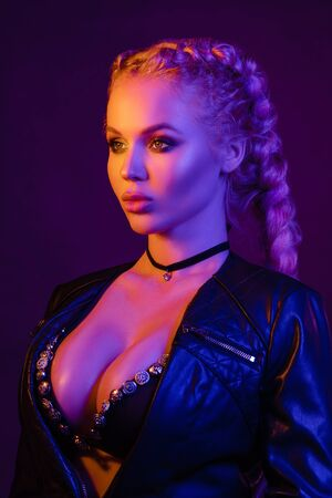 Photo for Portrait of seductive young European woman surrounded by evening neon lights medium close-up - Royalty Free Image