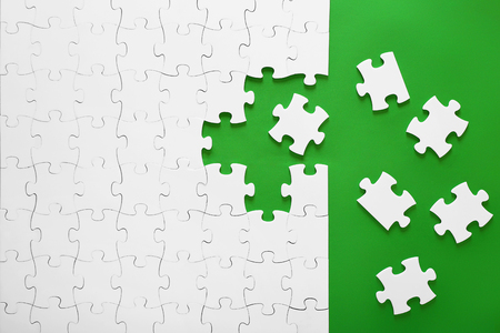 Photo pour White puzzles on a green background. The puzzle pieces are put together. The header, the template for a business idea. Teamwork in the organization. - image libre de droit