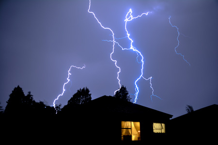 Photo pour Cloud to Ground Electric Lightning behind house roof tops - image libre de droit