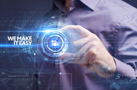 Foto de Business, Technology, Internet and network concept. Young businessman working on a virtual screen of the future and sees the inscription: we make it easy - Imagen libre de derechos