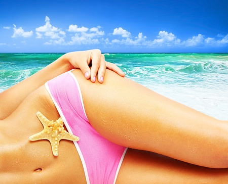Beautiful female body on the beach, conceptual image of vacation, spa, travel & summertime holidays