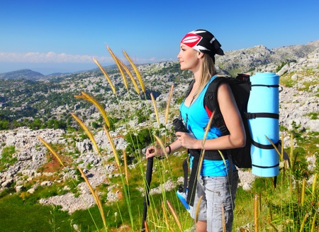 Traveling girl with backpack hiking in the mountains, eco tourism, freedom concept