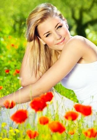 Lovely happy female closeup portrait, sitting in the poppy flower field, enjoying nature, summertime leisure concept