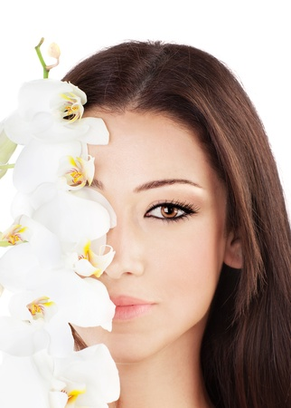 Closeup on beautiful face with white orchid flower, perfect clean skin, young female portrait,  isolated on white background with white text space, beauty and spa concept