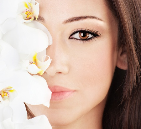 Closeup on beautiful face with white orchid flower, perfect clean skin, young female portrait, beauty and spa concept