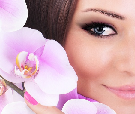 Half face of gorgeous young model, beautiful woman eye with fresh pink orchid flower,  part of female head, sexy girl with stylish look, spa and beauty background