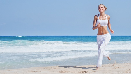 Foto de Healthy woman running on the beach, girl doing sport outdoor, happy female exercising, freedom, vacation, fitness and heath care concept with copy space over natural background - Imagen libre de derechos