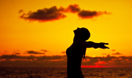 Woman silhouette over sunset sky, dark black shadow of female body with hands up, teenage girl having fun outdoor, enjoying sundown on the beach, freedom lifestyle, happiness concept