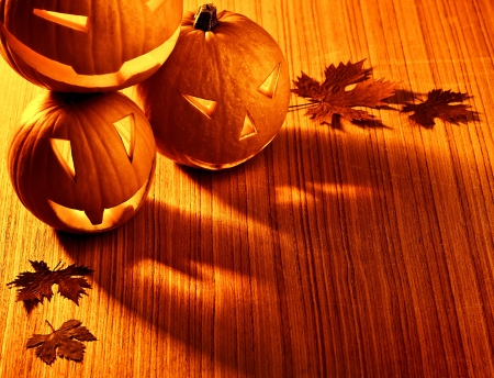 Picture of halloween glowing pumpkins border, three orange carved pumpkins and old dry leaves on wooden background, scary holiday shadow, traditional halloween decoration, jack-o-lantern