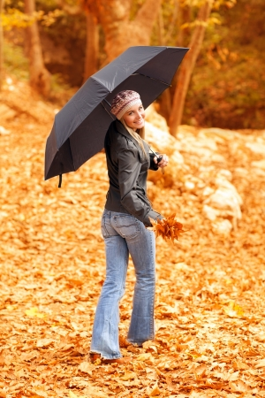 Image of attractive young lady standing under black umbrella in autumn forest in rainy weather, active healthy woman wearing colorful warm hat, nice blond girl holding dry autumnal leaves in hand