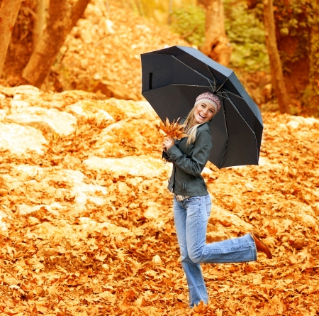 Image of happy female walking under umbrella in rainy day in autumnal park, cheerful blond girl in stylish hat dancing with black parasol in fall forest, usual autumn weather, spend time outdoor