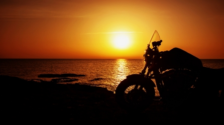Photo pour Picture of luxury motorcycle on the beach in night, silhouette of motorbike on sunset - image libre de droit