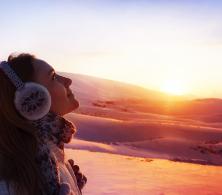 A pretty woman walking in snowy mountains, side view of cute girl looking up, closeup portrait of female wearing warm winter earmuff, red sunset, wintertime sports, trekking and hiking concept
