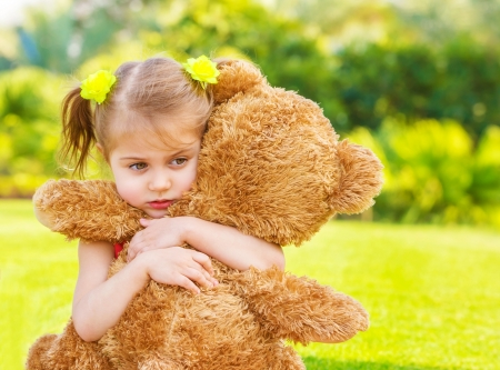 Photo for Little cute sad girl holding in hands brown teddy bear, upset child spending time outdoors in spring time - Royalty Free Image