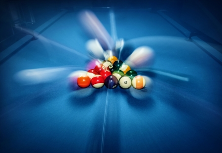Blue billiard table with colorful balls, beginning of game, slow motion, soft focus, snooker bar, entertainment in nightclub, hobby and sport concept
