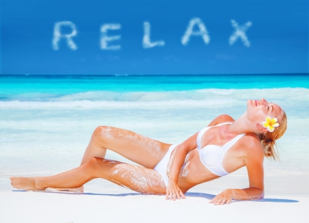 Girl relaxing on the beach with fresh frangipani flower in blond hair, taking sunbath, relaxation on luxury spa resort, summer vacation concept