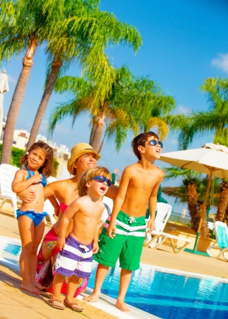 Foto de Cute big family standing near poolside and look up in the sky, enjoying summer holiday, facial expression, relaxation on the beach, love and friendship concept - Imagen libre de derechos