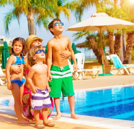 Photo pour Cute happy family having fun near pool on luxury tropical resort, mother with children looking up in sky, summer holidays, love concept - image libre de droit
