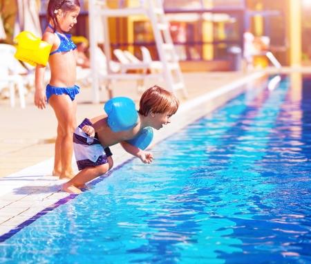 Foto de Cute little boy jumping into the pool, brother and sister having fun in poolside, water amusement, luxury beach resort, summer vacation, happy childhood - Imagen libre de derechos