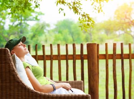Foto de Cute girl resting on veranda, young traveler woman sleeping on backyard in sanatorium, relaxation outdoors, luxury resort, pleasure concept - Imagen libre de derechos