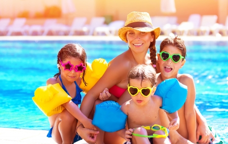 Happy big family having fun at the pool, spending summer vacation together, wearing funny colorful sunglasses, enjoyment and pleasure concept