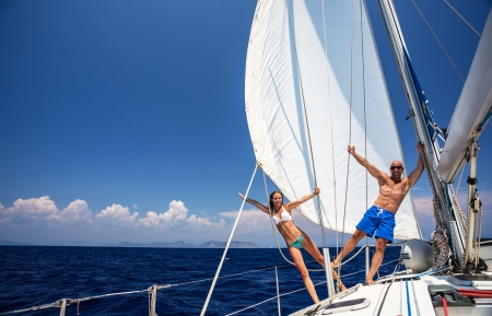 Photo pour Happy couple having fun on sailboat, young family in water cruise, yachting sport, active lifestyle, summer vacation, romantic trip, travel and tourism concept  - image libre de droit