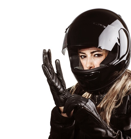 Foto de Closeup portrait of blond woman wearing motorsport outfit, isolated on white background, shiny black helmet and leather gloves, protective clothing  - Imagen libre de derechos
