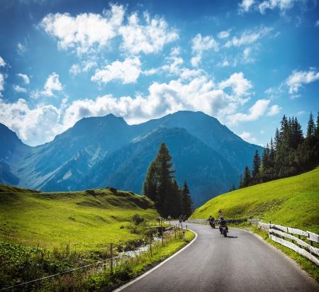 Photo pour Group of motorbikers in the mountains, race on mountainous highway, beautiful landscape, trip along Alps, travel and tourism concept - image libre de droit
