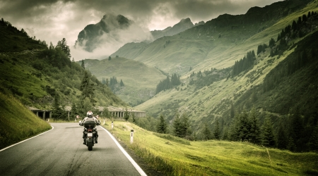 Photo for Motorcyclist on mountainous highway, cold overcast weather, Europe, Austria, Alps, extreme sport, active lifestyle, adventure touring concept - Royalty Free Image