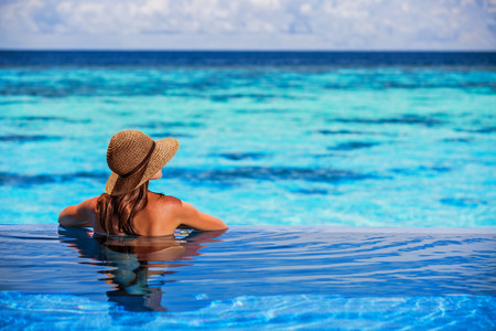 Photo for Having fun on beach resort, back side of sexy woman enjoying seascape from the pool, luxury summer vacation, travel and tourism concept - Royalty Free Image