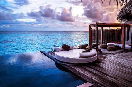Photo pour Luxury beach resort, bungalow near endless pool over sea sunset, evening on tropical island, summer vacation concept - image libre de droit