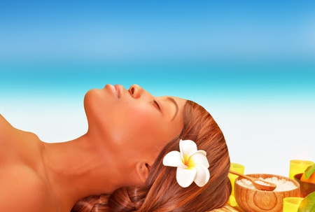 Closeup portrait of attractive African woman lying down on massage table on the beach in luxury spa resort, summer vacation concept