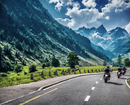 Photo pour Motorcyclists on mountainous road, enjoying tour along Alps, summertime activities, wonderful mountain landscape, extreme vacation concept - image libre de droit