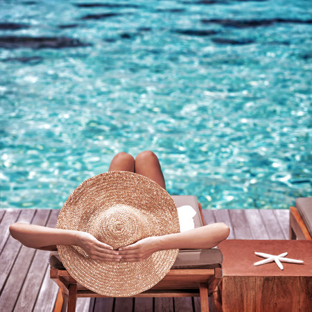 Photo pour Young woman sitting on wooden pier on the sea wearing hat and taking sun bath, enjoying perfect summer day, traveling and luxury vacation concept - image libre de droit