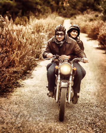 Foto de Vintage style image of two happy bikers riding on the road, active family enjoying journey on luxury extreme transport, freedom concept - Imagen libre de derechos