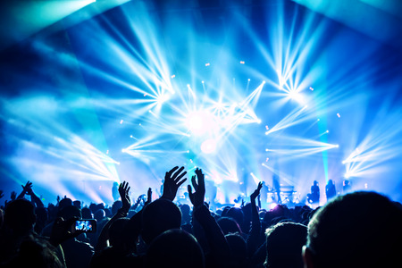 Photo for Large group of happy people enjoying rock concert, clapping with raised up hands, blue lights from the stage, new year celebration concept - Royalty Free Image