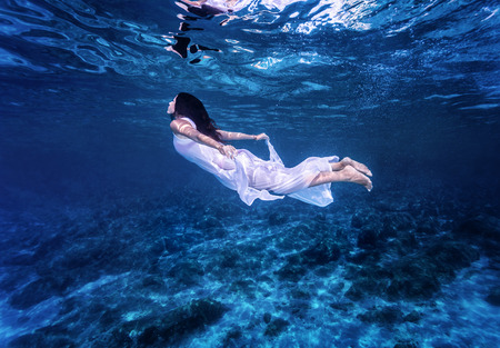 Photo pour Swimming in beautiful blue sea, gentle woman in white fashion dress diving underwater, refreshment and enjoyment concept - image libre de droit