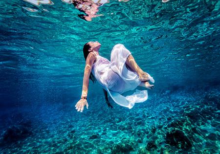 Photo pour Gorgeous female dancing underwater, wearing long white fashion dress, summer activity, relaxation in blue transparent sea, enjoyment and refreshment concept - image libre de droit