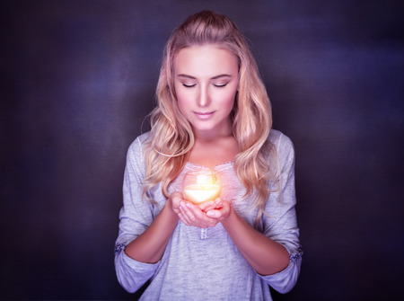 Photo pour Attractive woman with candle on dark background, calm girl with closed eyes praying, Christmas holidays concept - image libre de droit