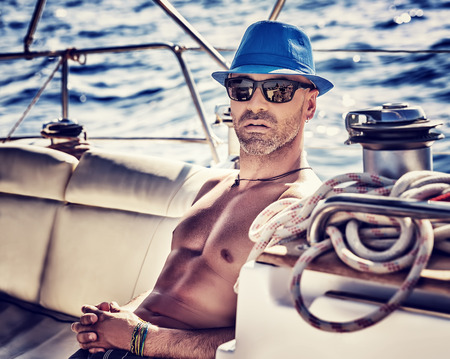 Foto de Sexy sailor, man on sailboat enjoying cruise, vintage style photo of a handsome shirtless model sailing on a luxury water transport, fashion lifestyle concept - Imagen libre de derechos