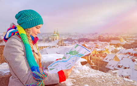 Foto de Cute traveler girl searching right direction on the map, standing on the roof of building and enjoying beautiful winter cityscape, travel to Prague - Imagen libre de derechos