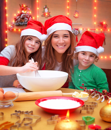 Portrait of cheerful young family preparing to Christmas dinner, mother with two kids cooking at home wearing Santa hat