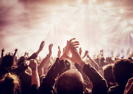 Foto de Vintage style photo of a crowd, happy people enjoying rock concert, raised up hands and clapping of pleasure, active night life concept - Imagen libre de derechos