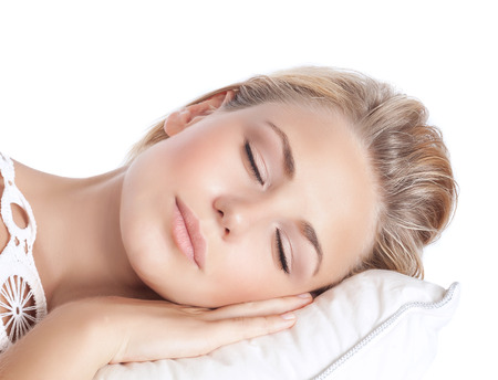 Foto de Closeup portrait of cute blond serene girl sleeping, attractive gentle female with closed eyes lying down on the pillow isolated on white background, peace and harmony concept - Imagen libre de derechos