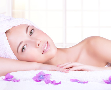 Photo pour Closeup portrait of beautiful woman with lying down on massage table, enjoying dayspa, natural beauty treatment, luxury spa salon, healthy lifestyle - image libre de droit