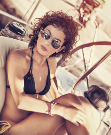 Foto de Stylish girl relaxing on sailboat, enjoying mild sunset light, luxury summer vacation, active lifestyle, having fun on sea cruise - Imagen libre de derechos