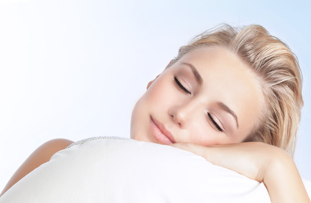 Foto de Closeup portrait of beautiful woman sleeping on the pillow isolated on blue and white background, happy calm day dreaming, conception of relaxation - Imagen libre de derechos