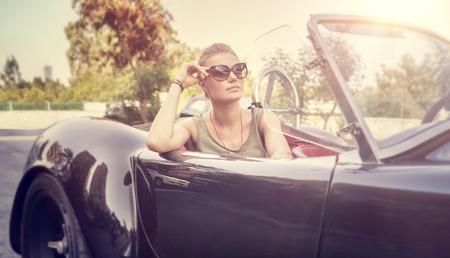 Photo pour Beautiful woman sitting in cabriolet - image libre de droit
