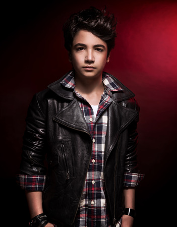 Photo for Stylish teen boy portrait over dark red background, handsome model wearing fashion shirt and leather jacket, funky adolescence style - Royalty Free Image