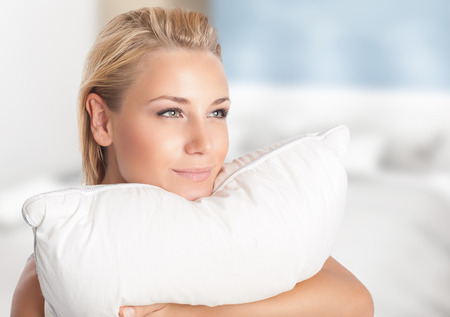 Photo pour Happy girl enjoying her favorite soft pillow, spending time at home, dreamy woman with pleasure preparing to sleep, resting on comfortable bedding - image libre de droit